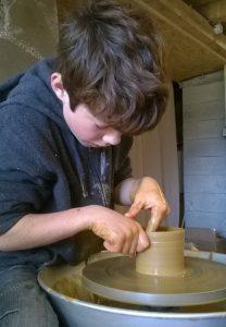 Pratique du tour de poterie par un enfant à l'atelier d'Autrans